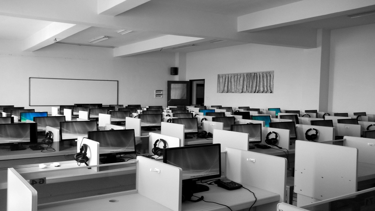 Black and white image of classroom full of work stations with desktop computers.