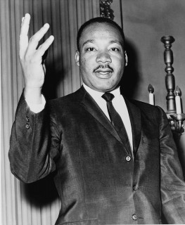 Black and white image of Dr. Martin Luther King, Jr. with one hand raised.