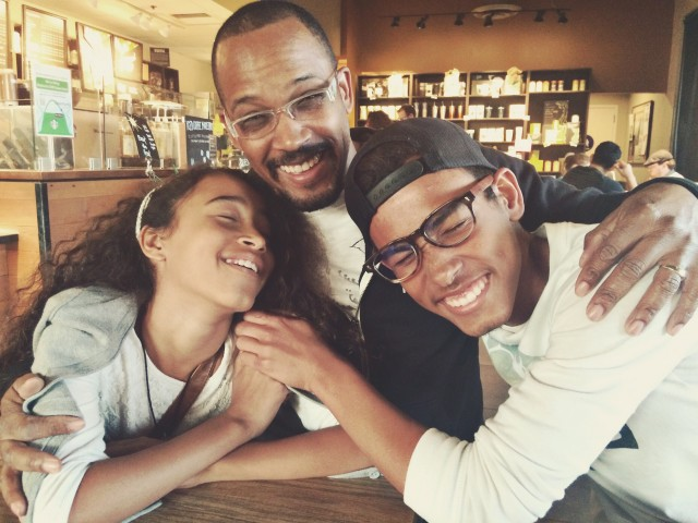 Teenage son and daughter hugging father in a coffee shop.