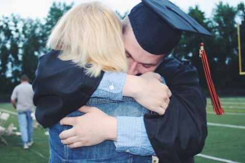 Son wearing graduation rob and cap hugging mother.