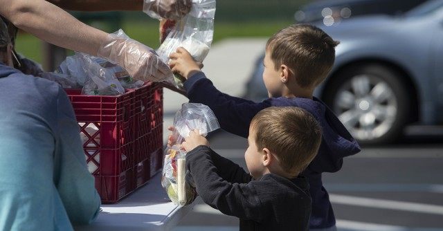 Two young boys holding bagged lunches representing food insecurity.